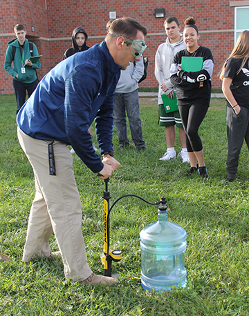 Geoscience+teacher+Tony+DeGrand+pumps+air+into+a+water+jug+to+help+show+how+clouds+form.%0APhoto+by+GG+Staff